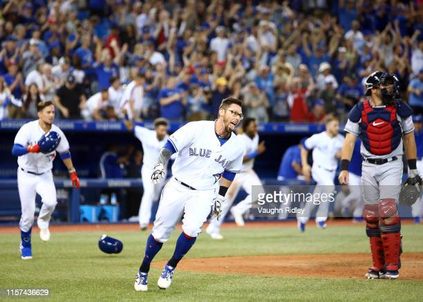 Eric Sogard of the Toronto Blue Jays scores the game winning run on a single by Justin Smoak in the tenth inning during a MLB game against the...
