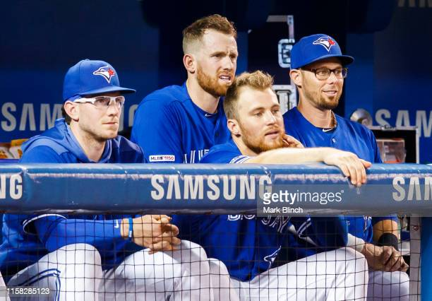 Eric Sogard of the Toronto Blue Jays stands behind teammates Danny Jansen, Billy McKinney, and Brandon Drury during play against the Tampa Bay Rays...