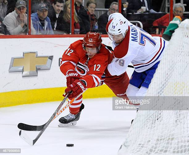 Eric Staal of the Carolina Hurricanes battles for the puck behind the net with Andrei Markov of the Montreal Canadiens during a game at PNC Arena on...