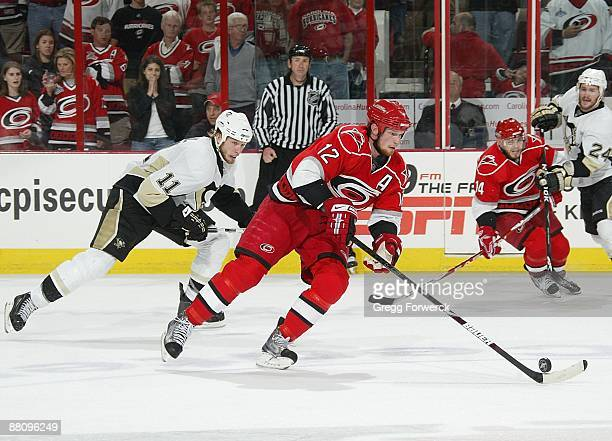 Eric Staal of the Carolina Hurricanes carries the puck ahead of brother Jordan Staal of the Pittsburgh Penguins during Game Four of the Eastern...