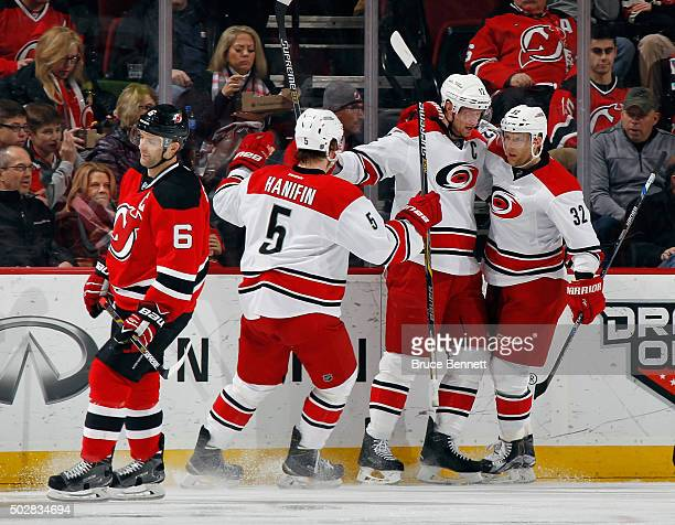 Eric Staal of the Carolina Hurricanes celebrates his goal at 251 of the second period against the New Jersey Devils along with Noah Hanifin and Kris...