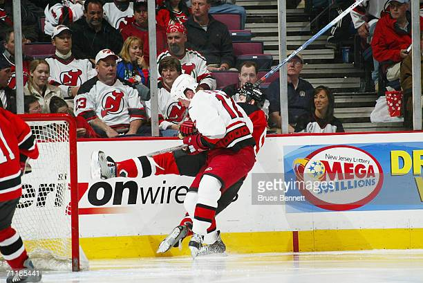 Eric Staal of the Carolina Hurricanes checks a New Jersey Devils player along the boards in game three of the Eastern Conference Semifinals during...