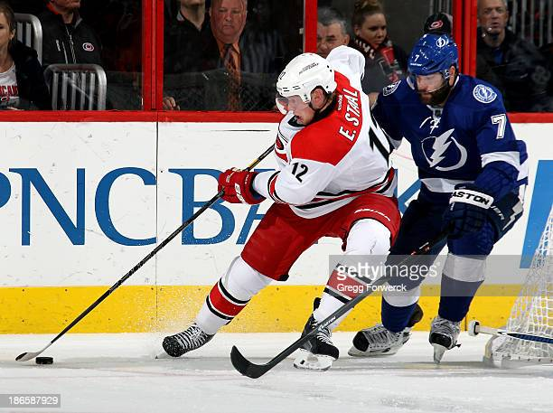 Eric Staal of the Carolina Hurricanes collects the puck at the side of goal while pressured by Radko Gudas of the Tampa Bay Lightning during their...