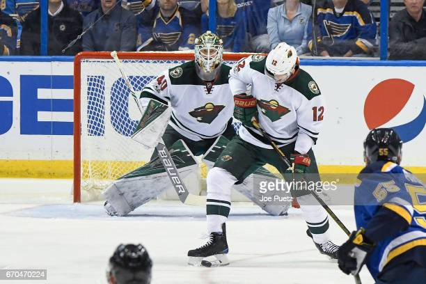 Eric Staal of the Minnesota Wild blocks a shot against the St Louis Blues as Devan Dubnyk of the Minnesota Wild looks on in Game Four of the Western...
