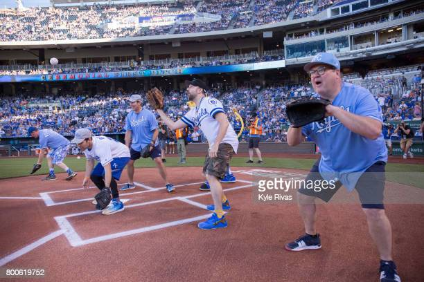 Eric Stonestreet Jason Sudeikis Paul Rudd Rob Riggle and David Koechner catch the first pitch during the Big Slick Celebrity Weekend benefitting...