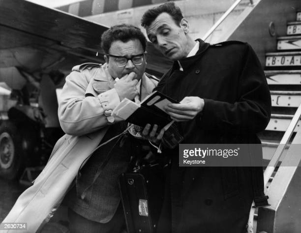 Eric Sykes the English comedy writer with Harry Secombe of 'Goon' fame at Heathrow airport puzzling over their passports They are leaving for a two...