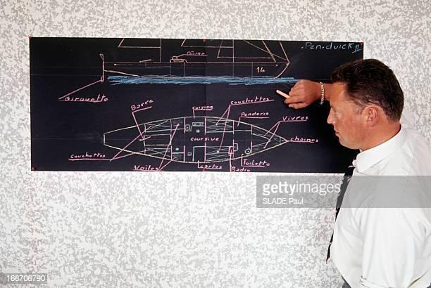 Eric Tabarly Wins The Transatlantic Solo Race Plymouth Newport 1964 Un homme nonidentifié de profil en chemise cravate tenant une craie debout près...