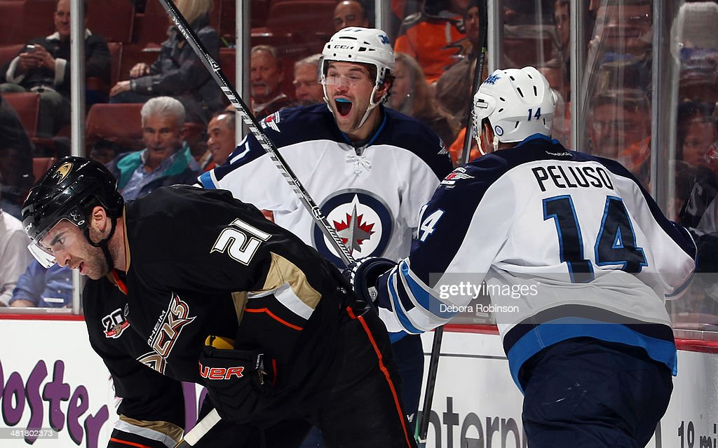 Eric Tangradi #27 and Anthony Peluso #14 of the Winnipeg Jets celebrate Tangradi's second-period goal as Kyle Palmieri #21 of the Anaheim Ducks skates away on March 31, 2014 at Honda Center in Anaheim, California.