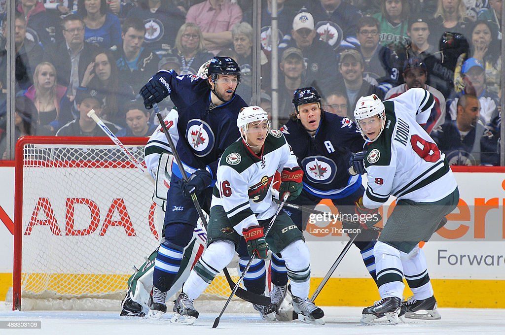 Eric Tangradi #27 and Olli Jokinen #12 of the Winnipeg Jets battle for position in front of the net against Jared Spurgeon #46 and Mikko Koivu #9 of the Minnesota Wild during third period action at the MTS Centre on April 7, 2014 in Winnipeg, Manitoba, Canada.