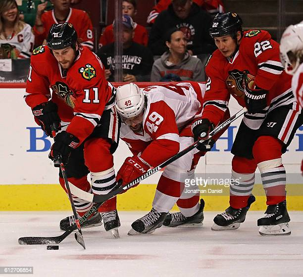 Eric Tangradi of the Detroit Red Wings tries to get to the puck between Andrew Desjardins and Jordin Tootoo of the Chicago Blackhawks during a...