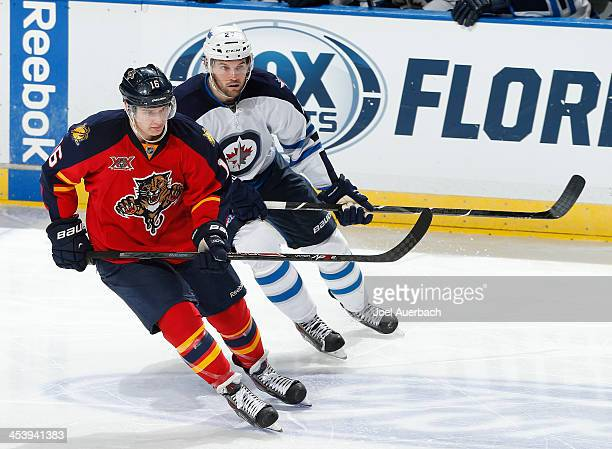 Eric Tangradi of the Winnipeg Jets and Aleksander Barkov of the Florida Panthers skate through center ice at the BBT Center on December 5 2013 in...
