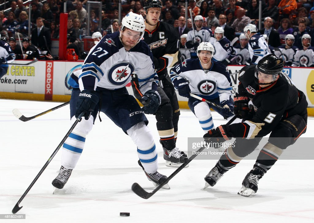Eric Tangradi #27 of the Winnipeg Jets battles for the puck against Luca Sbisa #5 of the Anaheim Ducks on March 31, 2014 at Honda Center in Anaheim, California.