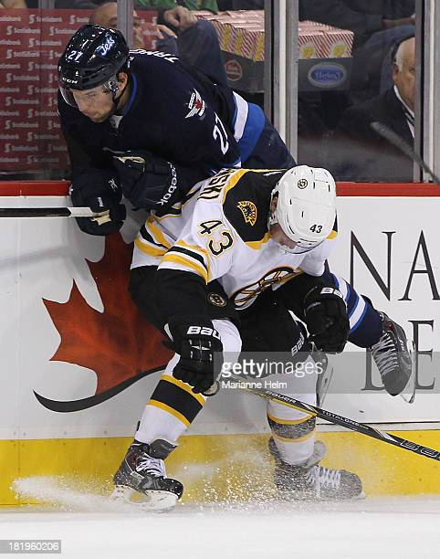 Eric Tangradi of the Winnipeg Jets is taken to the boards by Matt Bartkowski of the Boston Bruins in second period action during an NHL preseason...