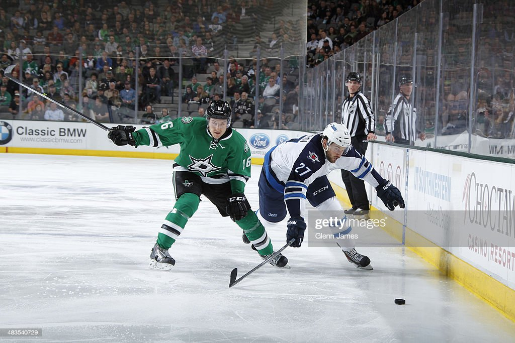 Eric Tangradi #27 of the Winnipeg Jets tries to keep the puck away against Ryan Garbutt #16 of the Dallas Stars at the American Airlines Center on March 24, 2014 in Dallas, Texas.