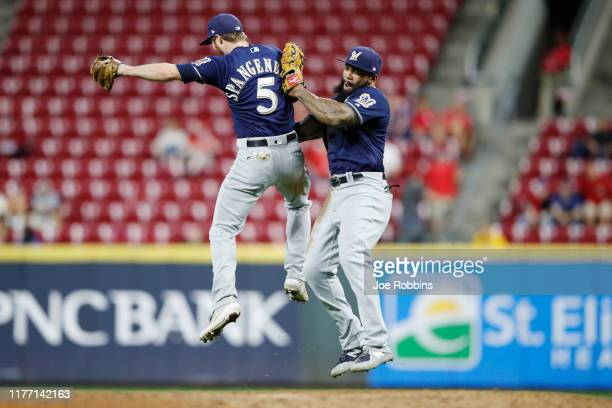 Eric Thames and Cory Spangenberg of the Milwaukee Brewers celebrate after clinching a playoff berth following a 9-2 win over the Cincinnati Reds at...