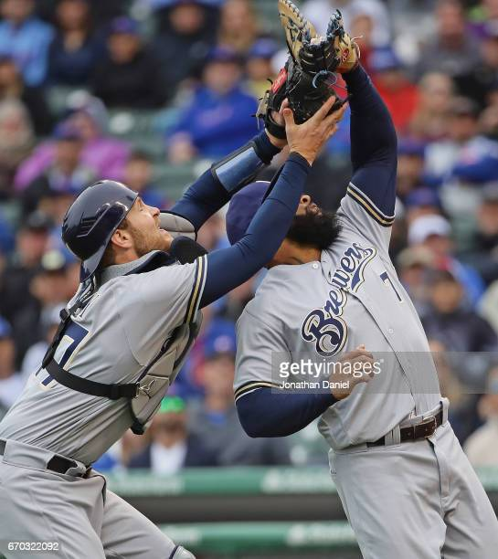 Eric Thames and Jett Bandy of the Milwaukee Brewers collide as Thames make a catch of a pop up in the 1st inning against the Chicago Cubs at Wrigley...