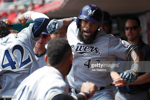 Eric Thames of the Milwaukee Brewers celebrates in the dugout after hitting a solo home run to tie the game in the third inning against the...