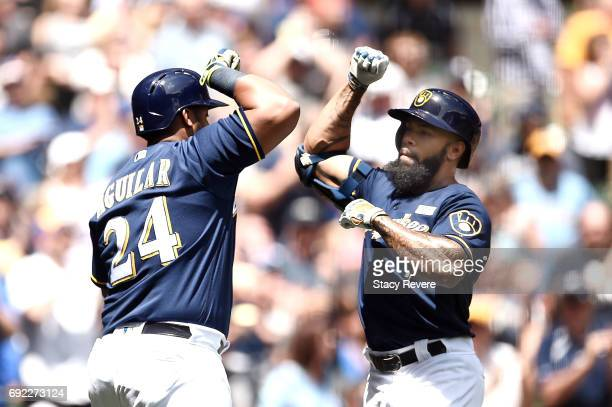 Eric Thames of the Milwaukee Brewers celebrates with Jesus Aguilar following a home run during the first inning of a game against the Los Angeles...