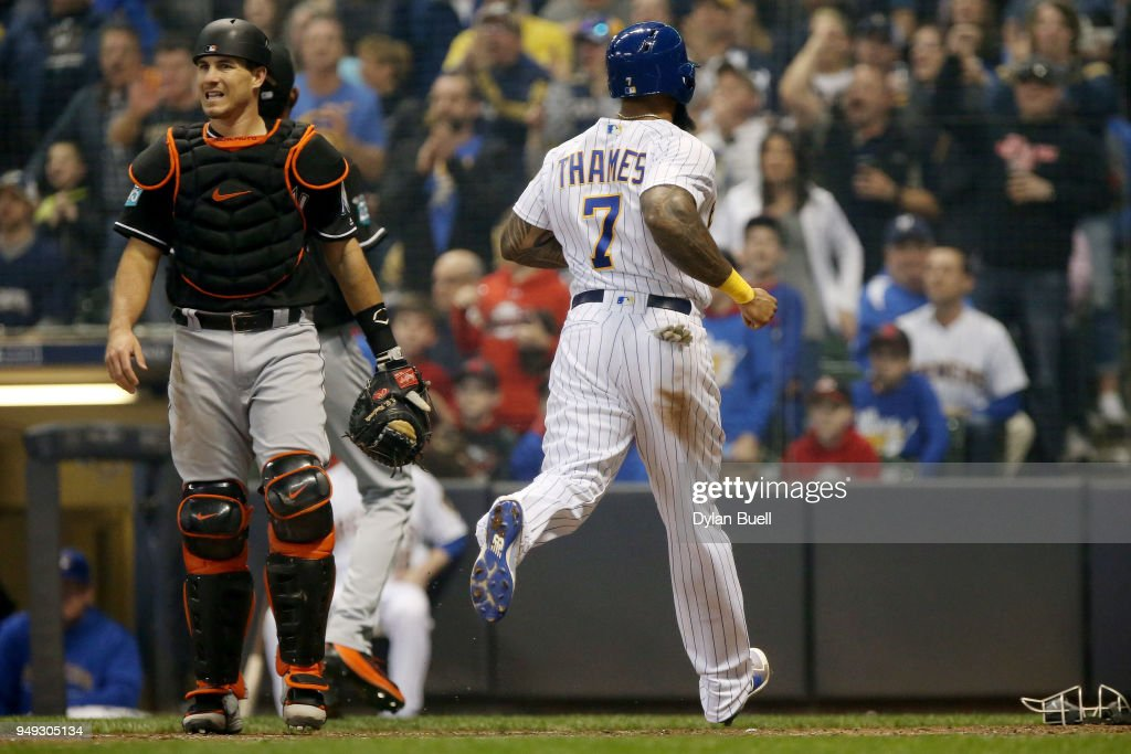 Eric Thames #7 of the Milwaukee Brewers scores a run past J.T. Realmuto #11 of the Miami Marlins in the fourth inning at Miller Park on April 20, 2018 in Milwaukee, Wisconsin.