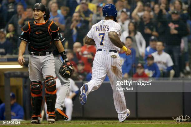 Eric Thames of the Milwaukee Brewers scores a run past JT Realmuto of the Miami Marlins in the fourth inning at Miller Park on April 20 2018 in...