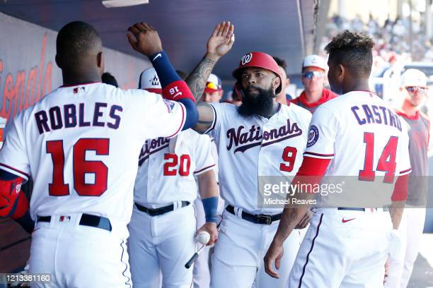 Eric Thames of the Washington Nationals celebrates with teammates after scoring a run against the New York Yankees during a Grapefruit League spring...