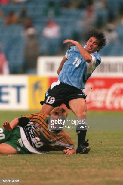 Eric Tinkler of South Africa tackles Antonio Pacheco of Uruguay
