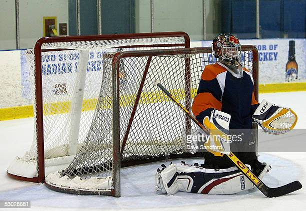 Eric Tobia of the Belleville Bulls wears a set of scaled down goaltending equipment as he stands in front of two goal nets the front one being...