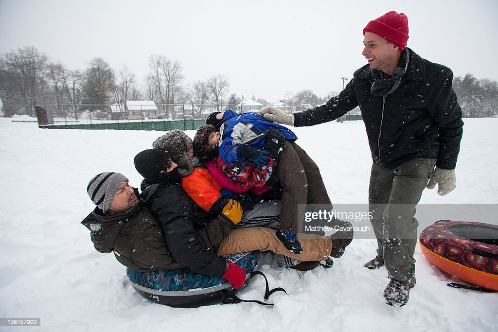 Eric Waite of Westborough, MA piles up kids on a friend's sled on December 27, 2012 in Greenfield, Massachusetts. A serious winter storm that caused tornados in the South on Christmas Day swept across the Northeast on Thursday, bringing snow, sleet, rain and causing dangerous travel conditions.
