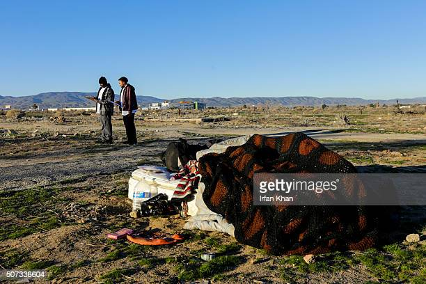Eric Washington left and Derrick Chambers check out a homeless encampment in an open area of Southern part of Lancaster while documenting their...
