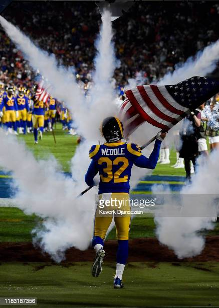 Eric Weddle of the Los Angeles Rams runs on the field waving a American flag before a game against the Chicago Bears at Los Angeles Memorial Coliseum...