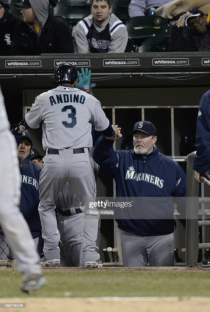 Eric Wedge #22 of the Seattle Mariners (R) congratulates Robert Andino #3 after he scored on an RBI single hit by Jesus Montero during the tenth inning against the Chicago White Sox on April 5, 2012 at U.S. Cellular Field in Chicago, Illinois. The Mariners won 8-7 in 10 innings.