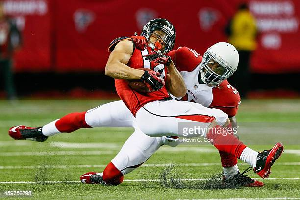 Eric Weems of the Atlanta Falcons is tackled by Antonio Cromartie of the Arizona Cardinals after a catch during the first half at the Georgia Dome on...