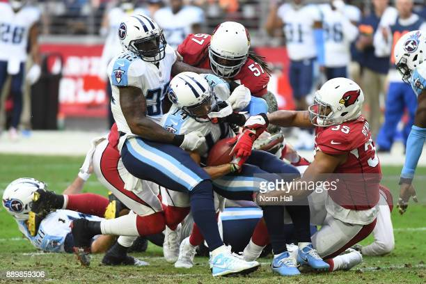 Eric Weems of the Tennessee Titans is tackled by Josh Bynes and Elijhaa Penny of the Arizona Cardinals in the second half at University of Phoenix...