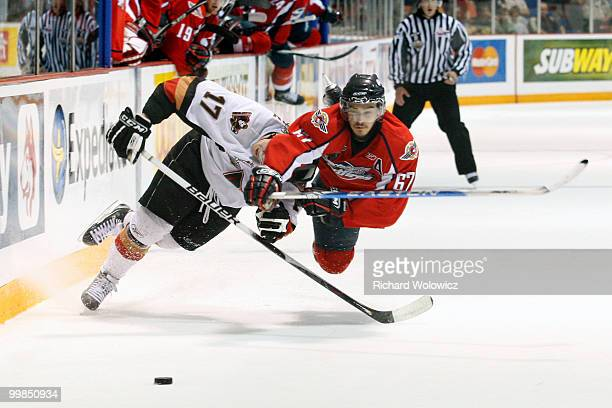 Eric Wellwood of the Windsor Spitfires body checks Giffen Nyren of the Calgary Hitmen during the 2010 Mastercard Memorial Cup Tournament at the...