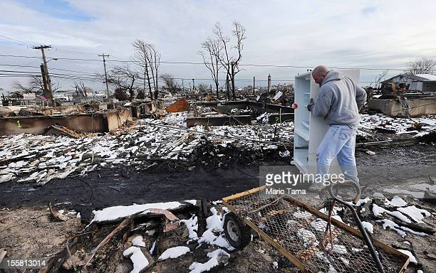 Eric White removes a refirgerator from father-in-law Dean Rasinya's damaged home located at the edge of a large fire that destroyed over 100 homes in...