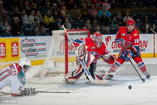 Eric Williams and Reid Gow of the Spokane Chiefs look for the rebound from a shot from Nick Merkley of the Kelowna Rockets during the third period on...