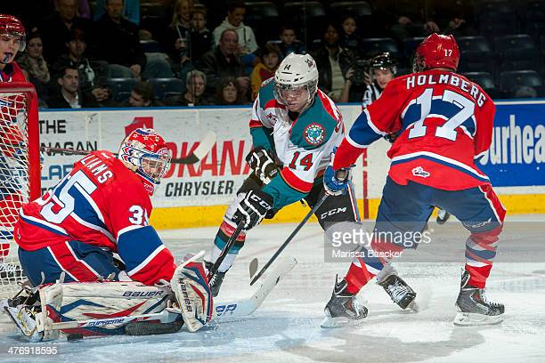 Eric Williams of the Spokane Chiefs deflects a shot from Rourke Chartier of the Kelowna Rockets as he is checked by Mitch Holmberg of the Spokane...