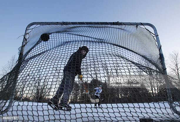 Eric Yemma, foreground, and David Parker take practice shots on goal at dusk at Rogers Pond in Kennebunk on Wednesday, January 18, 2012.