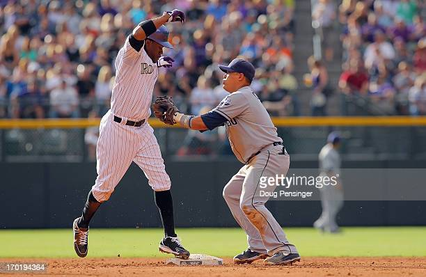 Eric Young Jr. #1 of the Colorado Rockies beats the tag of shortstop Everth Cabrera of the San Diego Padres as he is safe on a double steal allowing...