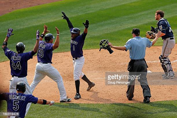 Eric Young Jr #1 of the Colorado Rockies celebrates after scoring the game winning run with Wilin Rosario of the Colorado Rockies on a walk off...