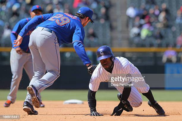 Eric Young Jr #1 of the Colorado Rockies gets tagged out in a rundown by second baseman Daniel Murphy of the New York Mets in the fourth inning at...