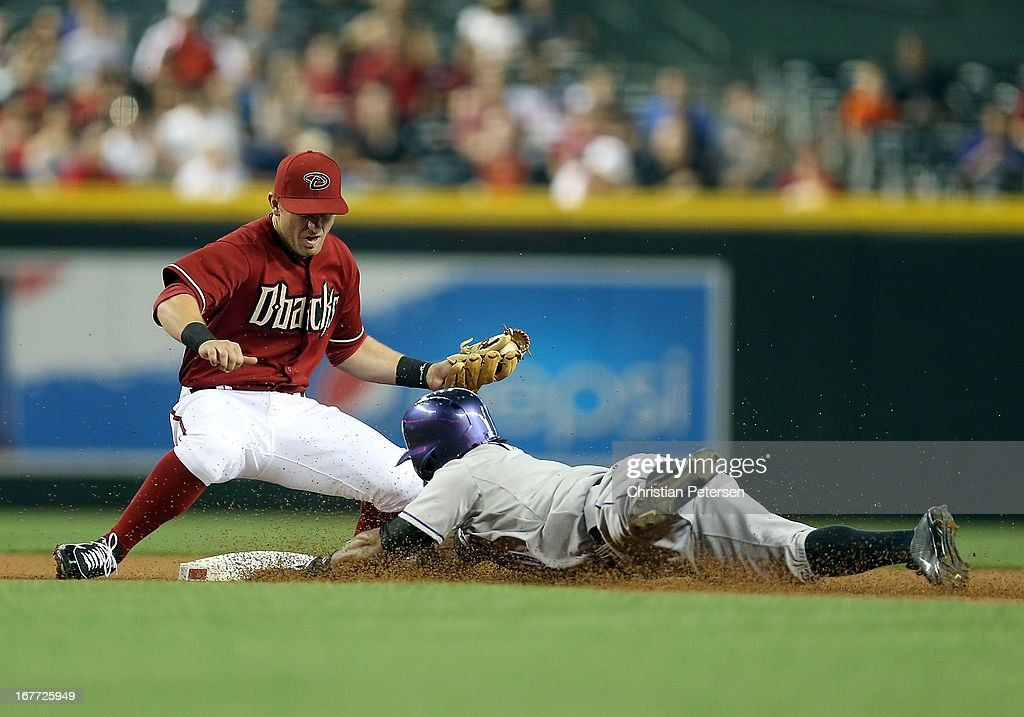 Eric Young Jr. #1 of the Colorado Rockies safely slides into the second base under infielder Cliff Pennington #4 of the Arizona Diamondbacks on a double during the first inning of the MLB game at Chase Field on April 28, 2013 in Phoenix, Arizona.
