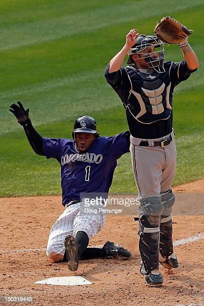 Eric Young Jr #1 of the Colorado Rockies slides home with the game winning run as catcher Jonathan Lucroy of the Milwaukee Brewers leaps for the...