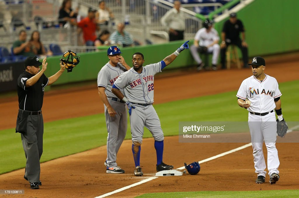 Eric Young Jr. #22 of the New York Mets appeals to home plate umpire Adam Hamari #78 that his triple was a home run as Placido Polanco #30 of the Miami Marlins looks on during a game at Marlins Park on July 31, 2013 in Miami, Florida.