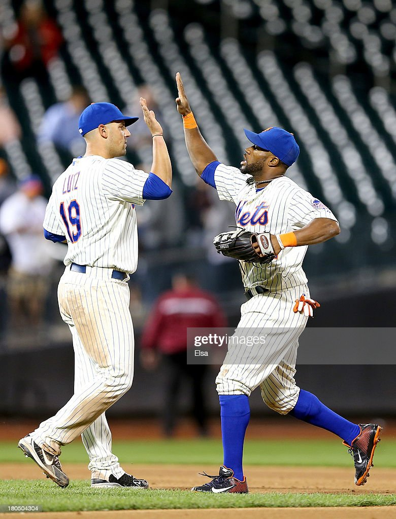 Eric Young Jr. #22 of the New York Mets celebrates the win with teammate Zach Lutz #19 on August 13, 2013 at Citi Field in the Flushing neighborhood of the Queens borough of New York City. The New York Mets defeated the Miami Marlins 4-3.