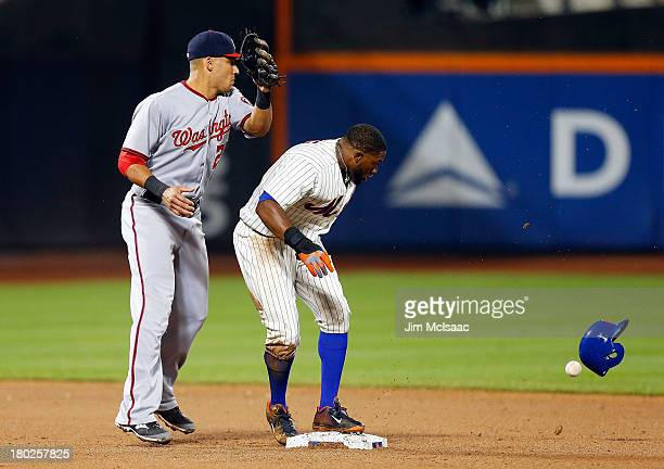 Eric Young Jr #22 of the New York Mets loses his helmet at second base as Ian Desmond of the Washington Nationals can't come with a ball thrown for...