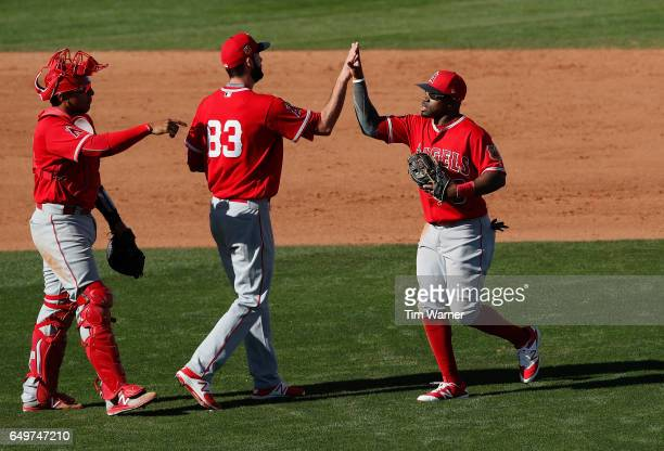 Eric Young Jr #8 of the Los Angeles Angels celebrates with Keynan Middleton and Jose Briceno after the spring training game against the Cincinnati...