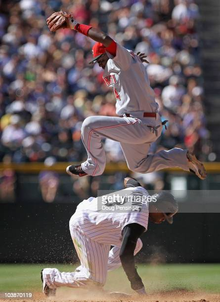 Eric Young Jr of the Colorado Rockies slides safely into second base as second baseman Brandon Phillips of the Cincinnati Reds is unable to catch the...
