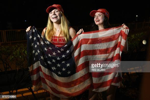 Erica Boland a US student based in Singapore and a supporter of US President Donald Trump and her friend wave a US flag as they wait for his arrival...