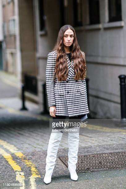 Erica Boldrin wears a black and white checked blazer jacket white high boots during London Fashion Week February 2019 on February 16 2019 in London...